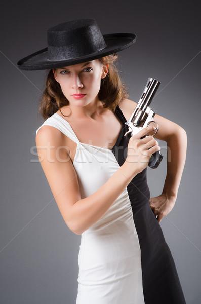 Woman with gun against dark background Stock photo © Elnur