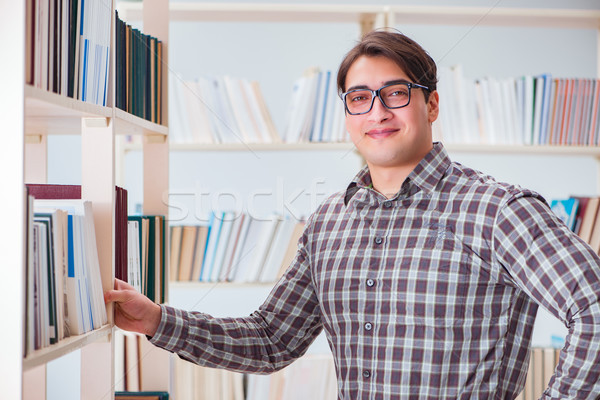 Stock photo: Young student looking for books in college library