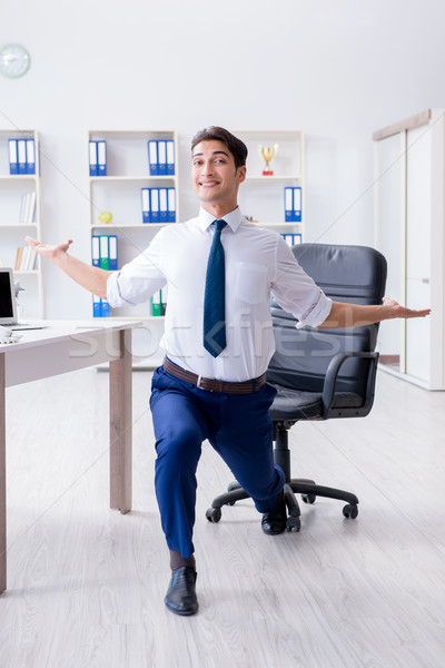Stock photo: Young businessman doing sports stretching at workplace