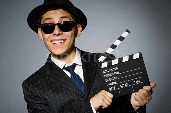 Young man in elegant suit holding clapperboard against gray Stock photo © Elnur