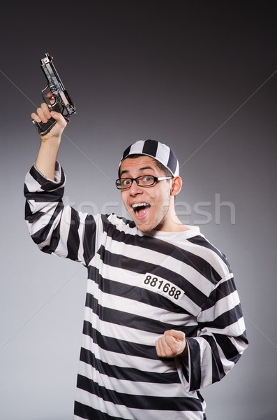 Funny prisoner with firearm isolated on gray Stock photo © Elnur