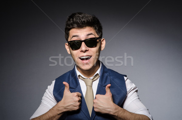 Stock photo: Young man in blue vest against gray