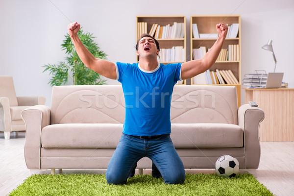 Adam izlerken futbol ev oturma kanepe Stok fotoğraf © Elnur