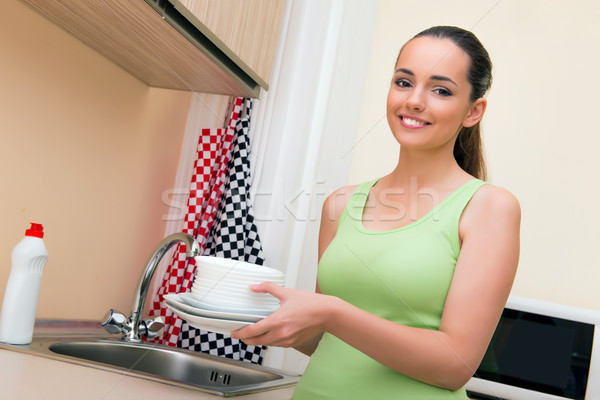 Young wife woman washing dishes in kitchen Stock photo © Elnur