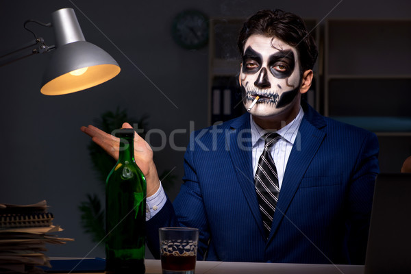 Businessman with scary face mask working late in office Stock photo © Elnur