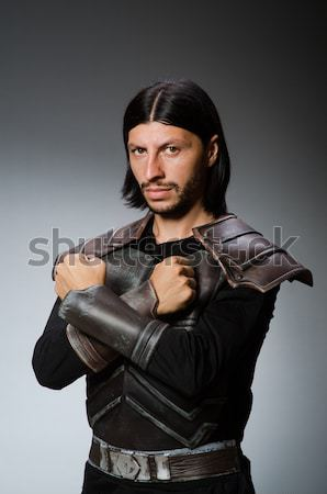 Angry knight with sword against dark background Stock photo © Elnur