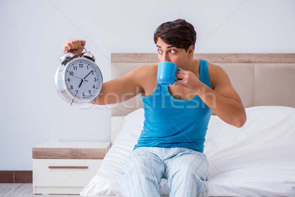 Young man waking up in bed Stock photo © Elnur