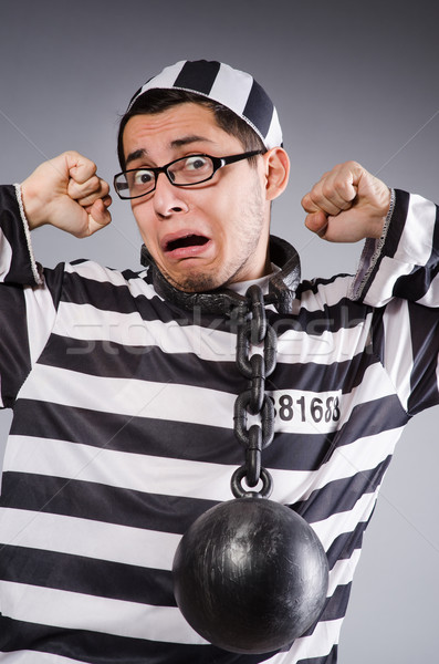 Stock photo: Funny prisoner in chains isolated on gray