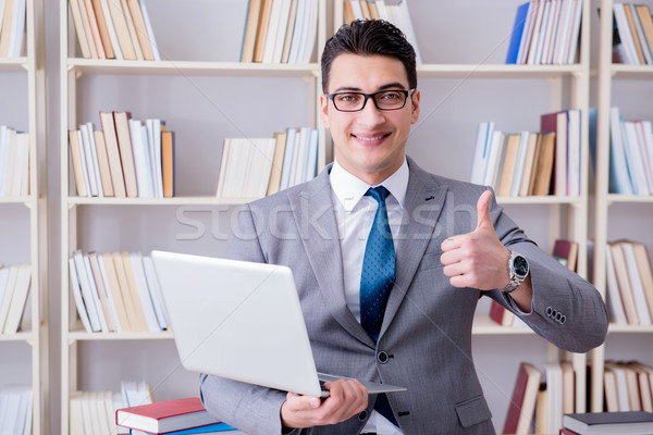 Businessman with a laptop working in the library Stock photo © Elnur