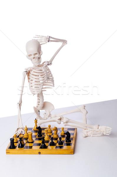 Skeleton playing chess game on white Stock photo © Elnur