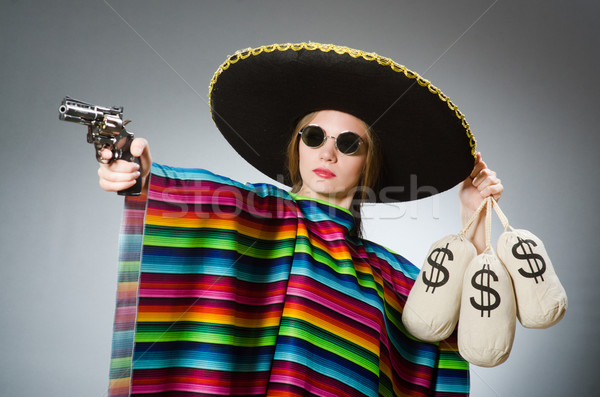 Girl in mexican poncho holding handgun and money sacks against g Stock photo © Elnur