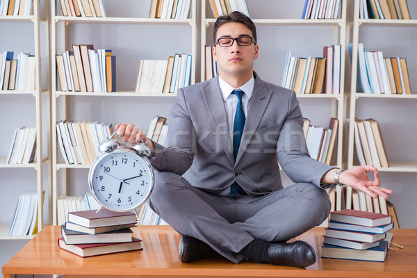 Businessman student in lotus position with an alarm clock in lib Stock photo © Elnur