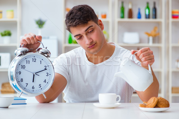 Man with alarm clock falling asleep at breakfast Stock photo © Elnur