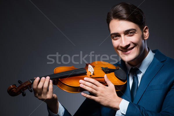Young man playing violin in dark room Stock photo © Elnur