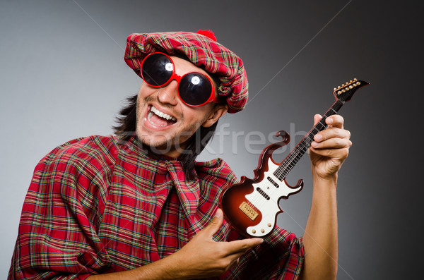 Funny scotsman playing red guitar Stock photo © Elnur