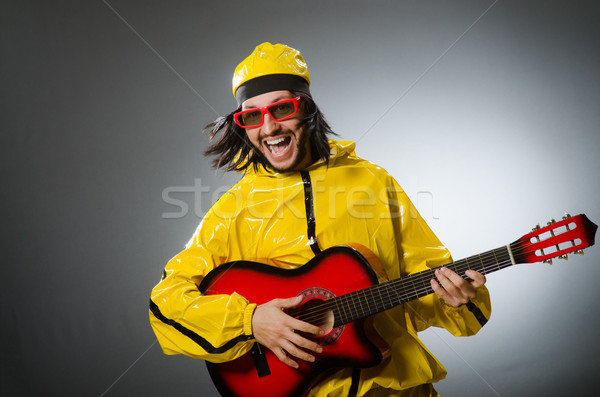 Funny man wearing yellow suit and playing guitar Stock photo © Elnur