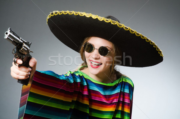 Girl in mexican vivid poncho with handgun against gray Stock photo © Elnur