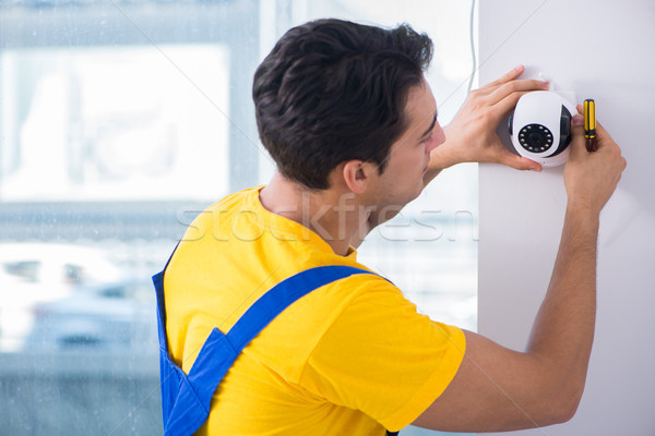 Contractor installing surveillance CCTV cameras in office Stock photo © Elnur