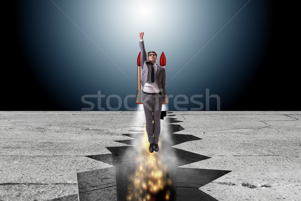 Businessman flying on rocket from rock gap Stock photo © Elnur