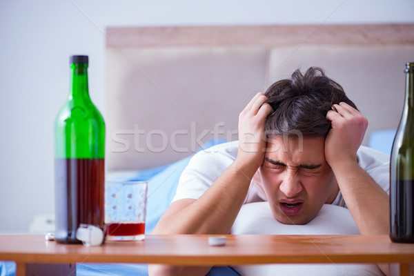 Man alcoholic drinking in bed going through break up depression Stock photo © Elnur