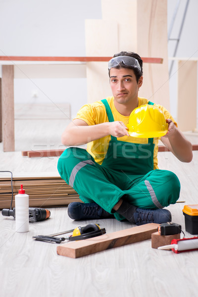 Carpenter wearing yellow hardhat in contractor workshop Stock photo © Elnur