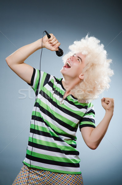 Man in afrowig singing with mic Stock photo © Elnur