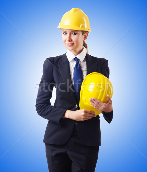 Young businesswoman with hard hat against gradient  Stock photo © Elnur