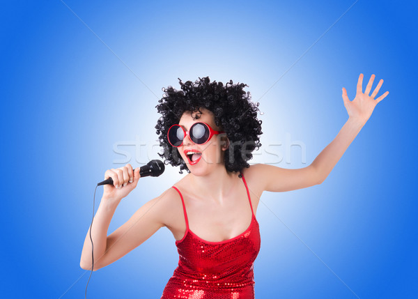 Pop star with mic in red dress against gradient  Stock photo © Elnur