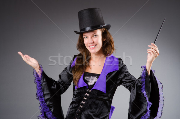 Pretty magician girl holding stick against gray Stock photo © Elnur