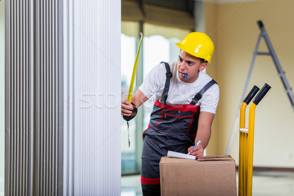 Delivery man taking dimensions with tape measure Stock photo © Elnur
