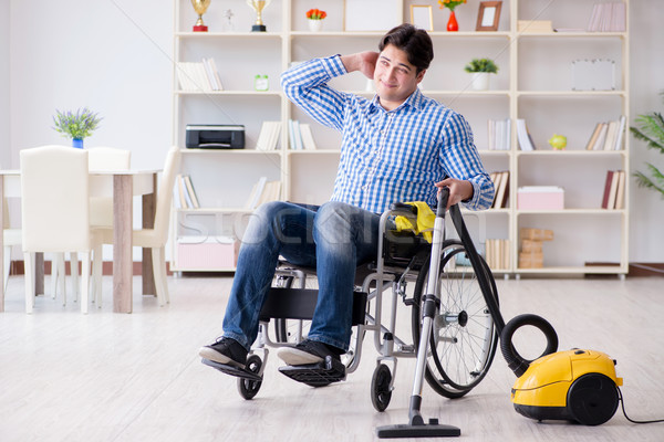 The disabled man cleaning home with vacuum cleaner Stock photo © Elnur