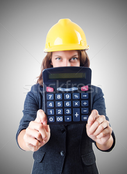 Female builder with calculator against gradient  Stock photo © Elnur