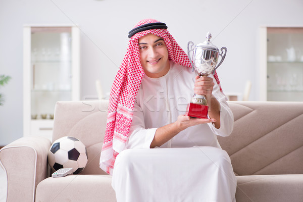 Stock photo: Young arab man watching football sitting on sofa