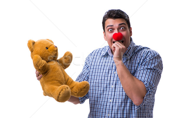 Stock photo: Funny clown man with a soft teddy bear toy isolated on white bac