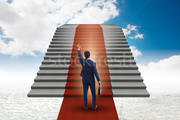 Young businessman climbing stairs and red carpet into sky Stock photo © Elnur