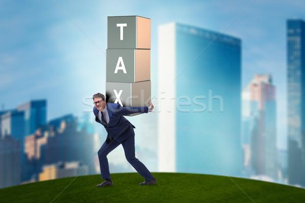 Businessman under heavy tax burden Stock photo © Elnur