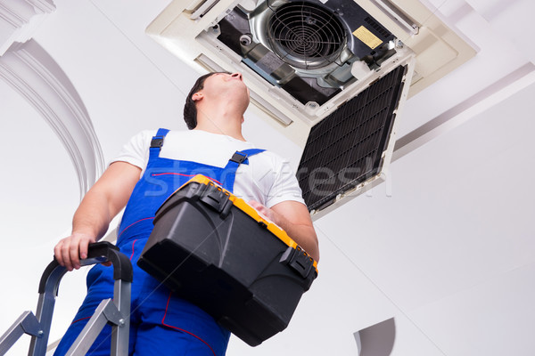 Worker repairing ceiling air conditioning unit Stock photo © Elnur