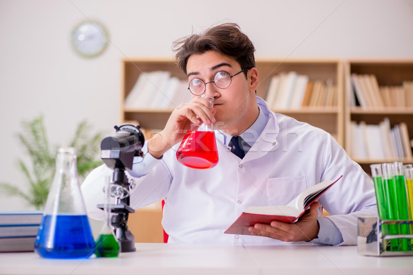 Stock photo: Mad crazy scientist doctor doing experiments in a laboratory