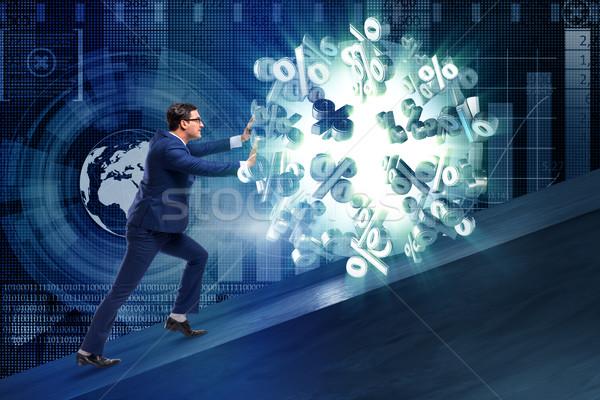 Businessman pushing away high interest rates Stock photo © Elnur