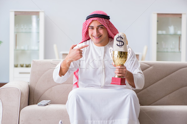 Arab man with prize and money on sofa Stock photo © Elnur