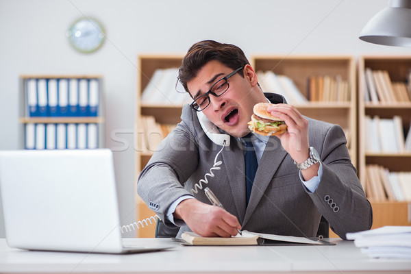 Głodny funny biznesmen jedzenie kanapkę Zdjęcia stock © Elnur