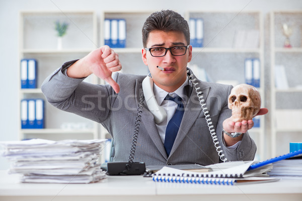 Businessman in the office smoking holding human skull Stock photo © Elnur