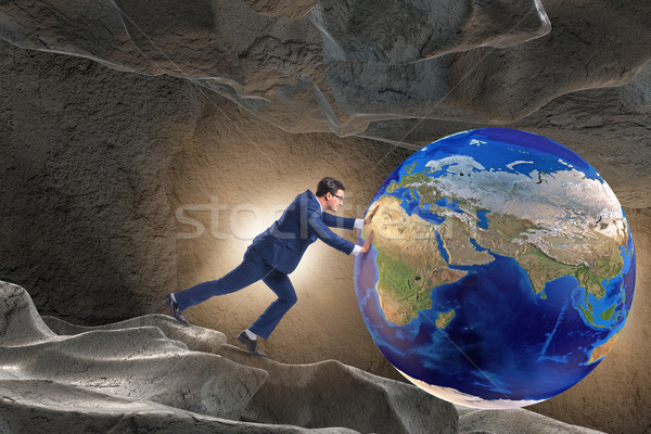 Businessman pushing the world in challenge concept Stock photo © Elnur