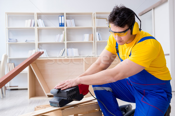 Repairman carpenter polishing a wooden board with an electric po Stock photo © Elnur