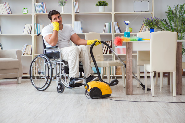 Disabled man with vacuum cleaner at home Stock photo © Elnur