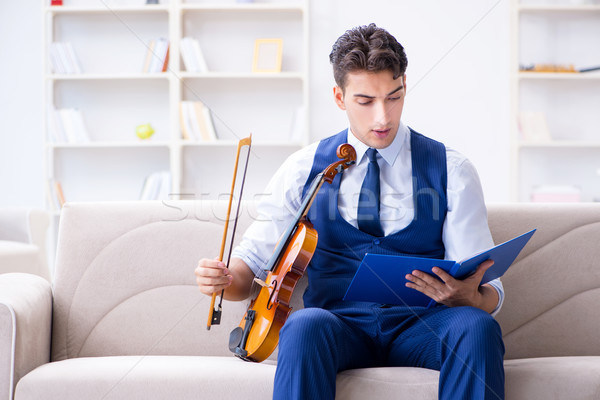 The young musician man practicing playing violin at home Stock photo © Elnur