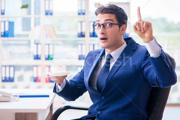 Businessman drinking coffee in the office during break Stock photo © Elnur