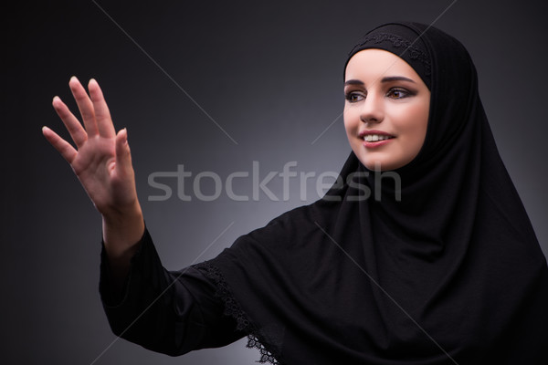 The muslim woman in black dress against dark background Stock photo © Elnur
