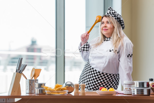 Female cook preparing soup in brightly lit kitchen Stock photo © Elnur