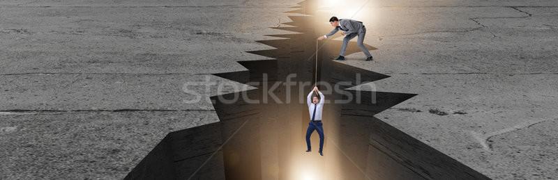 Man saving colleague pulling rope Stock photo © Elnur